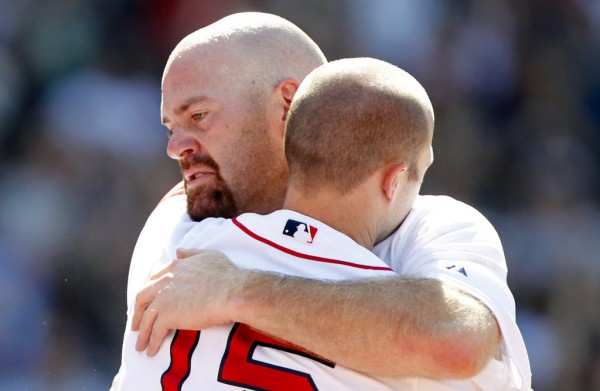 Boston Red Sox's Kevin Youkilis (left) hugs teammate Dustin Pedroia as Youkilis comes off the field after hitting a triple and being replaced with a pinch runner in the seventh inning of a baseball game against the Atlanta Braves in Boston Sunday, June 24, 2012.