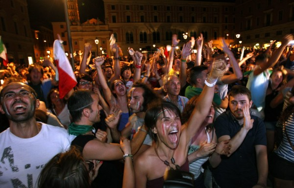 Italian soccer fans celebrate the team's victory as they watch the Euro 2012 soccer championship quarterfinal match between England and Italy on a giant screen in Rome on Sunday, June 24, 2012.