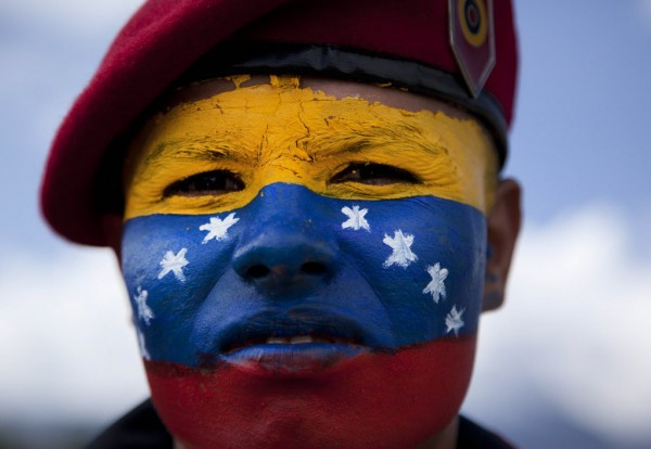 A soldier with his face painted with the colors of the Venezuelan flag attends a military parade at the military academy in Fuerte Tiuna, Caracas, Venezuela Sunday, June 24, 2012.