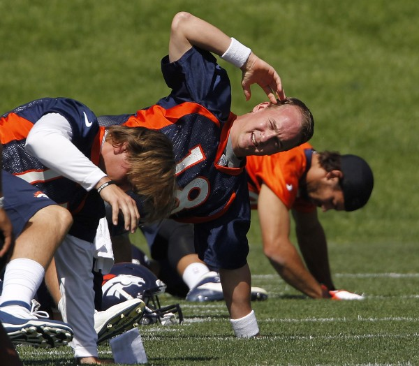 Denver Broncos quarterback Peyton Manning (18) stretches with teammates at practice at the team's training facility in Englewood, Colo., on Monday, June 4,  2012.