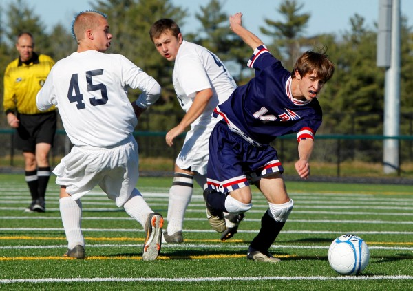 Bangor Christian's Brad Wilcox slips through Greenville defenders Trevor Richards (45) and Nathan Fenn in the Class D soccer state final last season in Falmouth, Wilcox, who holds the state record for career goals, is taking his soccer skills to Lancaster Bible College this fall.