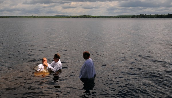 Paul Stuckey (right) waits in the water for the baptism of his wife, Laura Stuckey, (left) by Pastor Jerry Mick of the Bangor Baptist Church. The church has an annual traditional baptism ceremony at the home of a parishioner on Pushaw Lake in Orono.
