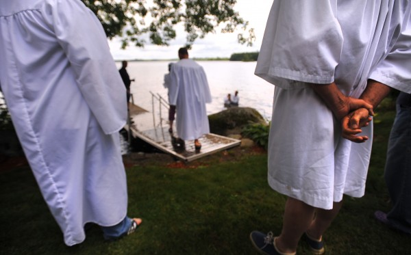 People wait for their turn during a traditional baptism ceremony held by the Bangor Baptist Church on Pushaw Lake in Orono.