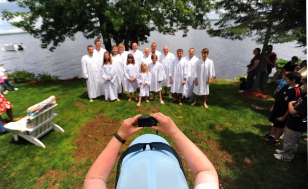 The group of people who are about to get baptized gather for a picture with Bangor Baptist Church Pastor Jerry Mick before the ceremony in Orono Sunday.