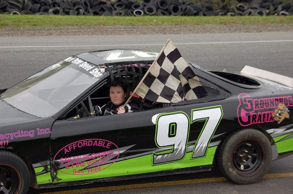 Becky Elston of Carmel holds the checkered flag after winning a Sport Four race at Speedway 95 in Hermon last year. Elston currently is second in the Sport Four points race this season.