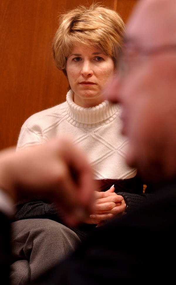 Sue Bernard, spokeswoman for the Roman Catholic Diocese of Portland, listens as Bishop Joseph Gerry speaks with a reporter at the diocese's offices in Portland in June 2001.