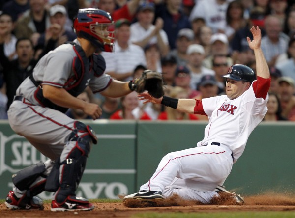 Boston Red Sox's Daniel Nava, right, scores on a hit by Dustin Pedroia as Atlanta Braves' David Ross waits for the throw in the second inning of a baseball game in Boston, Saturday, June 23, 2012.