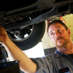 Bill Duncanson, lead technician at D&M Auto Repair on Congress Street in Portland, works on a car in the shop Tuesday.