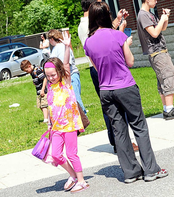 Emilie Levasseur races past her mother, Sarah, and other parents waiting to take photos on her final day as a first-grader at Geiger Elementary School in Lewiston on June 11, 2012.