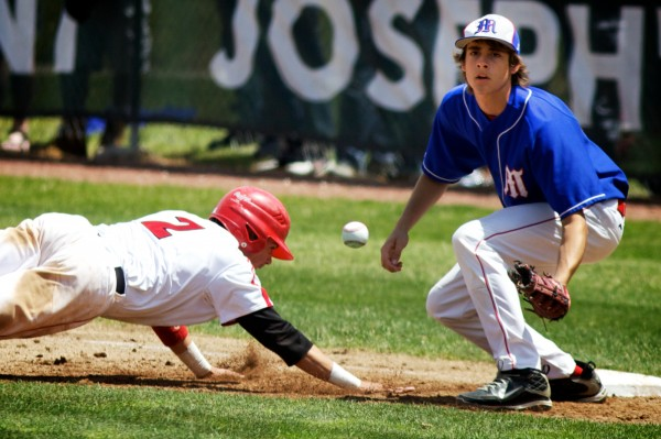 Sacrborough High School's Joseph Cronin dives back to first base on Saturday, June 16, 2012 as Messalonskee High School's Taylor Clark waits for the ball during the State Class A Baseball Championship Game.