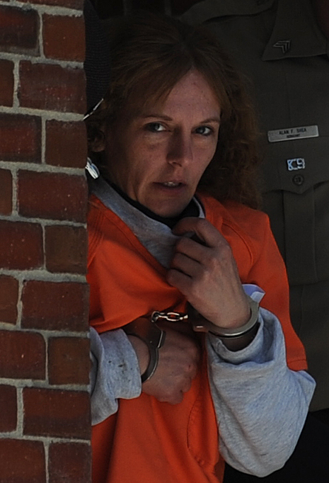 Corina Durkee peeks as she exits the Lincoln County Courthouse in Wiscasset on Friday, April 24, 2009.  She was escorted to a car to return her to jail after her inital appearance in the murder of Rachel Grindal of Waldoboro.