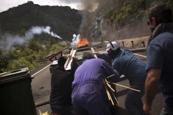 Miners fire handmade rockets at riot police officers as they defend their position after blocking a road in Cinera, near Leon, Spain, on Tuesday, June 19, 2012. Striking Spanish coal miners firing homemade rockets and using slingshots have clashed with authorities in northern Spain, driving officers out a town where the miners cut off a highway and railroad service.