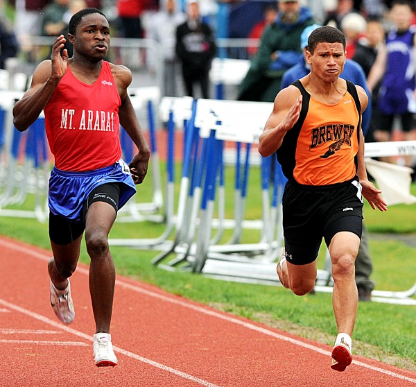 Mount Ararat's Darine Gnidehoue attempts to keep pace with Brewer's Anthony Jackson in the 100-meter dash Saturday at the Class A State Track Championship in Windham.