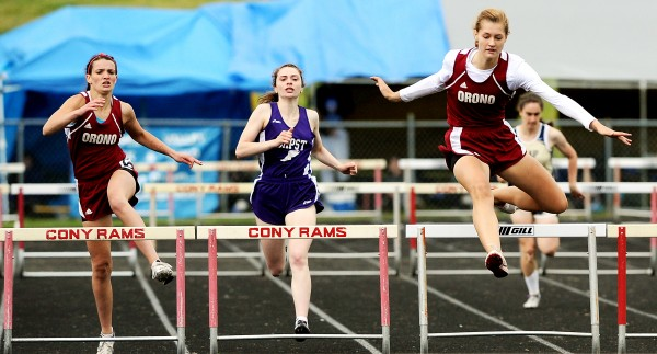 Orono's Abby Weigang (right) sails over the hurdle just before teammate Kayla Marquis (left) and competitor Ciara Petrello from John Bapst during the fourth section of the 300-meter hurdles at the Class C State Championships in Augusta Saturday.