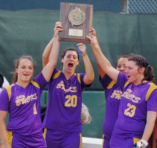 Eastern Maine regional softball champions, the Bucksport High School Lady Bucks (from left to right) Sadie Wight (1), Bailey Blair (20), Taylor Gauvin (7) and Shelby Redman (23) hold the trophy high after defeating Calais High School on Tuesday evening, June 12, 2012 at Coffin Field in Brewer.