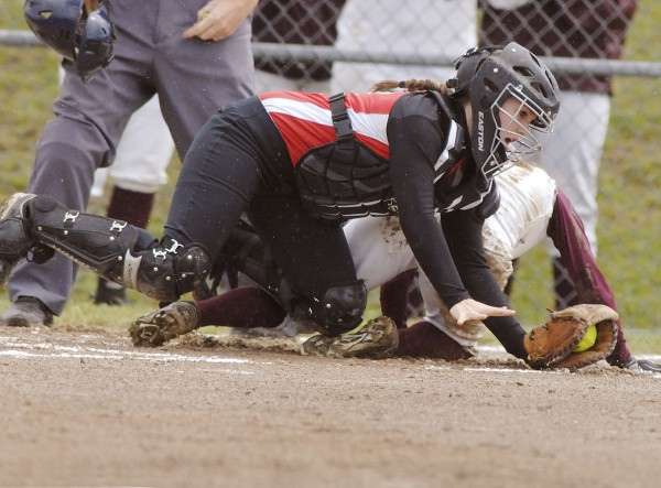 Camden Hills' High School softball catcher Natalie Hamalainen falls after a collision at home plate with Ellsworth runner Heather Holt (4). Holt scored from third base on a double steal play in the first inning of their game in Ellsworth, Maine, Tuesday June 5, 2012.
