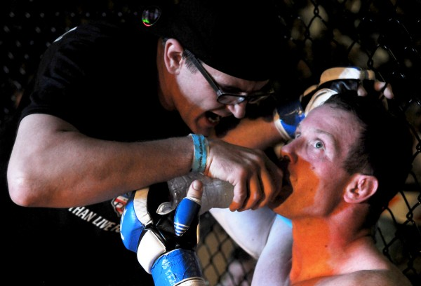 Trainer Ryan Cowette gives John Raio a pep talk and a drink of water between rounds of an amateur mixed martial arts bout at the Biddeford Arena in April 2012.