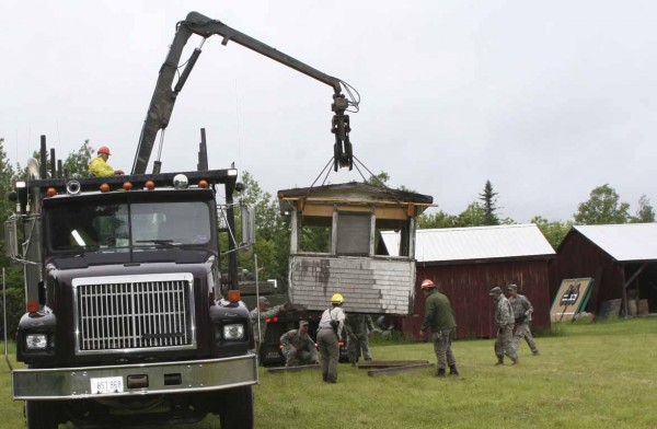 A state fire watch tower, which stood for 98 years on Norway Bluff west of Oxbow in Aroostook County, now calls the Ashland Logging Museum home, following its relocation on June 13, 2012, by members of the Maine Forest Service and Maine Army National Guard. Rafford Trucking transported the structure in two pieces, with forest rangers and guardsmen, shown here, working together to unload the base and cab.