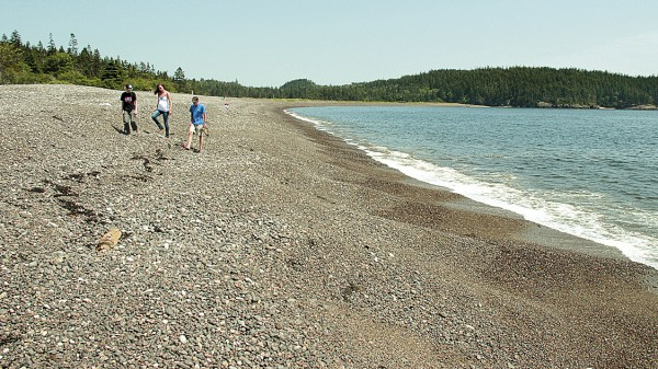 Visitors explore Jasper Beach in Machiasport. When the tide flows across its surface, this natural rock beach literally &quotrattles and rolls&quot as water-moved rocks clatter against each other.