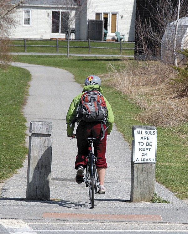 A bicyclist crosses an intersection along the South Portland Greenbelt Walkway.