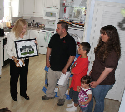 Virginia Manuel (left), state director for the U.S. Department of Agriculture Rural Development, presents a signed, framed photo of their new home to Chris and Erica Thibodeau of Madawaska and their children, Cyprian and Kristiana, on Friday, June 29, 2012.