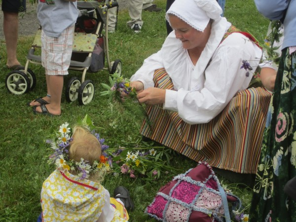 A woman works on a flower garland for her baby at the 2012 New Sweden Midsummer Festival.