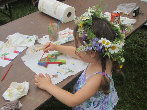 A girl paints a Dala horse in one of the activity tents at the 2012 New Sweden Midsummer Festival.
