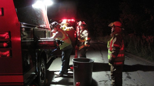 Firefighters refill air supply tanks in Stetson on Saturday night.