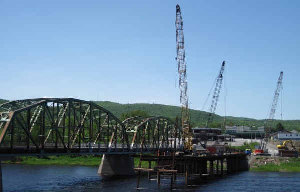 Cranes stand at the ready on the Canadian side of the St. John River across from Fort Kent as work continues on the new international bridge connecting Maine with Clair, New Brunswick. The project is jointly funded by the state and province and the old bridge will remain in limited use until construction is complete in August 2014.