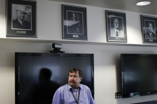 In a June 20, 2012 photo, Escondido police chief Jim Maher speaks below portraits of previous police chiefs at police headquarters in Escondido, Calif. Escondido, a city of 140,000 people, has 11 ICE employees assigned to its station around the clock to pursue immigration offenders, particularly those with criminal records.