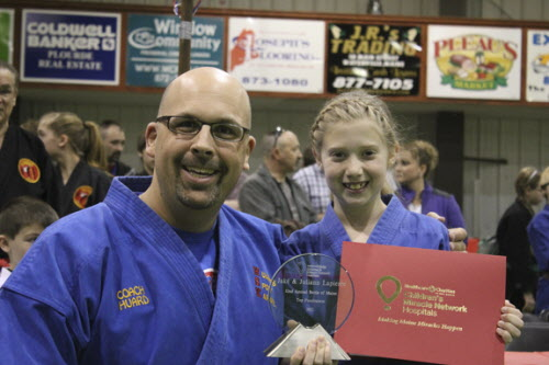 Juliann Lapierre of Winslow accepts the Top Fundraiser award from Coach Mark Huard at the Battle of Maine Martial Arts Championships held this spring in Winslow.