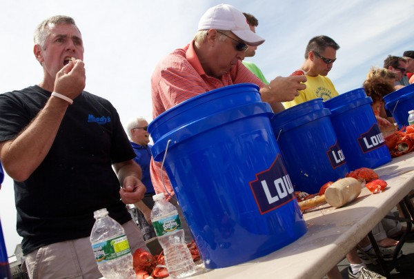 Contestants including Shawn Moody (left) race to eat as many lobsters as possible in ten minutes during a lobster-eating contest in Portland Saturday June 30, 2012. The fourth annual Portland Lobster Festival was organized by the Falmouth Rotary and took place on the Maine State Pier.
