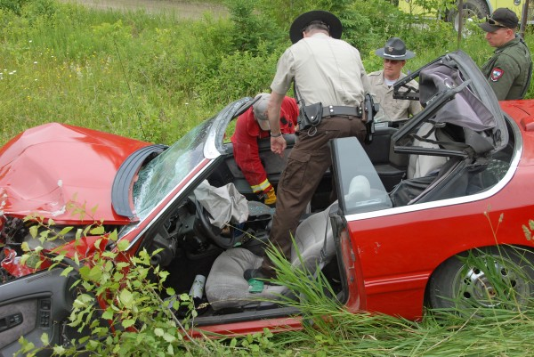 Lee Fire Chief Jay Crocker (from left), Penobscot County Sheriff''s Department Deputy Peter Stone and Sgt. William Birch hunt through a Chrysler LeBaron convertible destroyed in a two-vehicle collision on Route 6 in Lee on Saturday, June 23, 2012. Four females were hurt in the crash.
