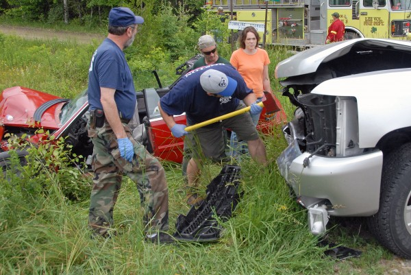 Lee firefighters including Crystal Willette (in orange shirt) work to pop open the hood of a Chevy Silverado pickup truck involved in a two-car crash on Route 6 in Lee on Saturday, June 23, 2012.