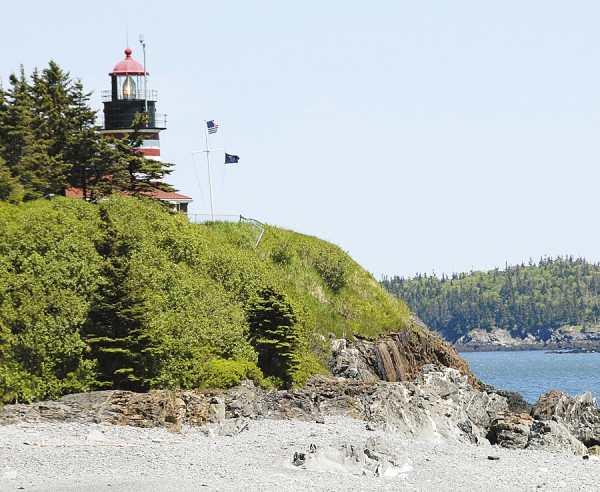 The light gleams from West Quoddy Head Lighthouse, perched above the rugged shore of West Quoddy Head in Lubec.