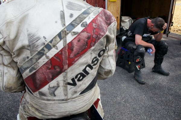 Scott Vile of Freeport rests after his second vintage motorbike race of the day in New Hampshire Monday June 11, 2012, behind friend Steve Baker, whose leathers bear the scars of many a tumble on the track.
