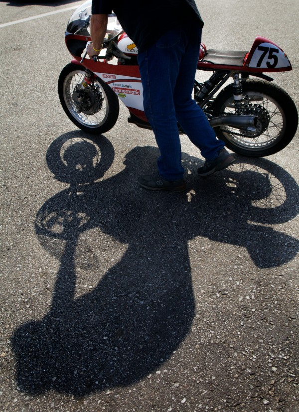 Kerry Smith's father, a retired motorcycle racer, pushes her bike toward the trailer at the end of a day of racing Monday, June 11, 2012, at New Hampshire Motor Speedway.