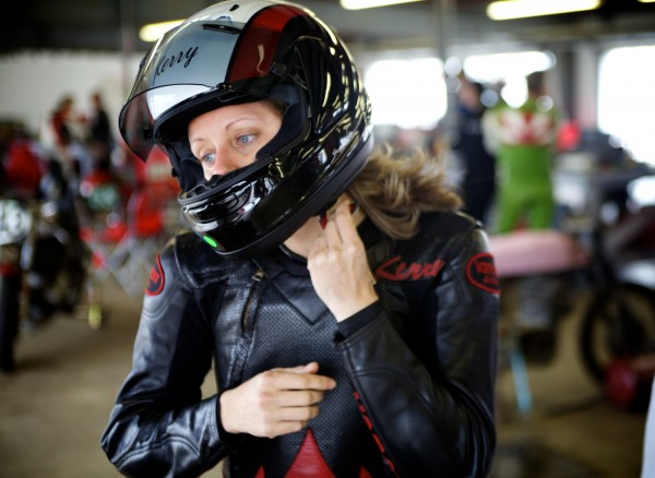 Kerry Smith, 31, puts on her helmet before a race Monday, June 11, 2012, in New Hampshire. Smith, who raises funds for United Way in Portland during the week, grew up watching her father race motorcycles on the weekends.