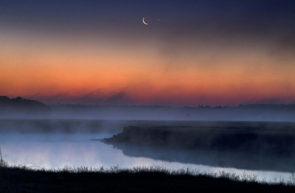 A crescent moon and the planet Jupiter rise in the eastern sky at dawn at the Scarborough Marsh Sunday, June 17, 2012.