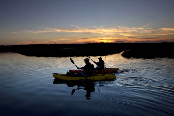 Phil Gasowski and his son, Bennett, 13, of Gorham paddle kayaks while fishing for striped bass at sunset on the Scarborough Marsh Friday, June 15, 2012.