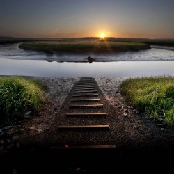 The sun rises over an oxbow curve at the Scarborough Marsh Sunday, June 17, 2012. A boat ramp leads to the water over the muddy bank in the foreground.
