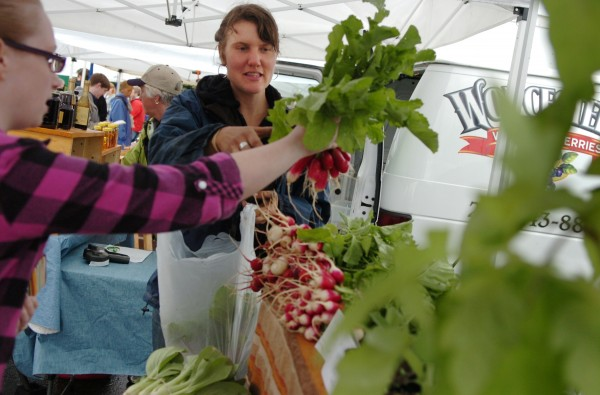 Molly Crouse of Nettie Fox Farm in Newburgh helps Samantha Fox of Winterport with the selection of radishes and Swiss chard during the Bangor farmers' market which made its debut Sunday afternoon, June 3, 2012.
