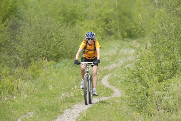 A woman pedals her mountain bike along the old Veazie Railroad bed in the Bangor City Forest.
