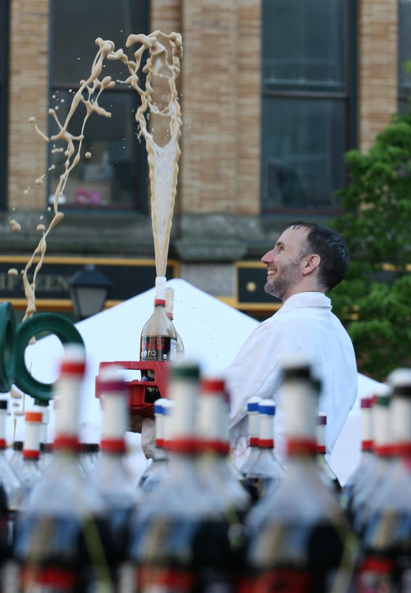 Fritz Grobe, one of the Coke and Mentos guys, sprays soda in the air as he does a demonstration before the start of the Extreme Diet Coke and Mentos Experiments on Thursday, June 28, 2012 in Monument Square in Portland. The performance involved over 100 bottles of soda and over 600 Mentos candies.