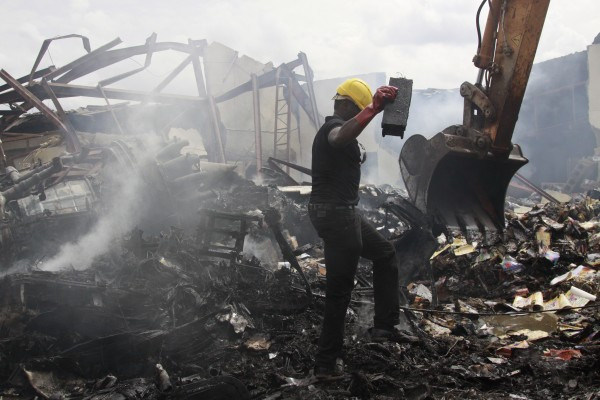 A rescue worker recovers an unidentified item from the site of a plane crash in Lagos, Nigeria, Monday, June 4, 2012.