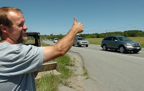 Matthew Perkins gives the thumbs up to a Union Street Towing driver (not pictured) after the towing company was getting ready to remove his truck and skid-steer trailer payload (seen behind him) after he was involved in an accident with another truck which apparently went over the centerline.