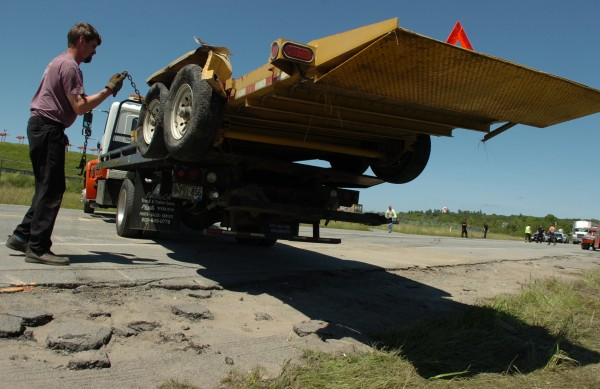 Union Street Towing's Chris Murray secures a detached trailer atop his employer's flatbed for haulaway Monday, June 18, 2012.