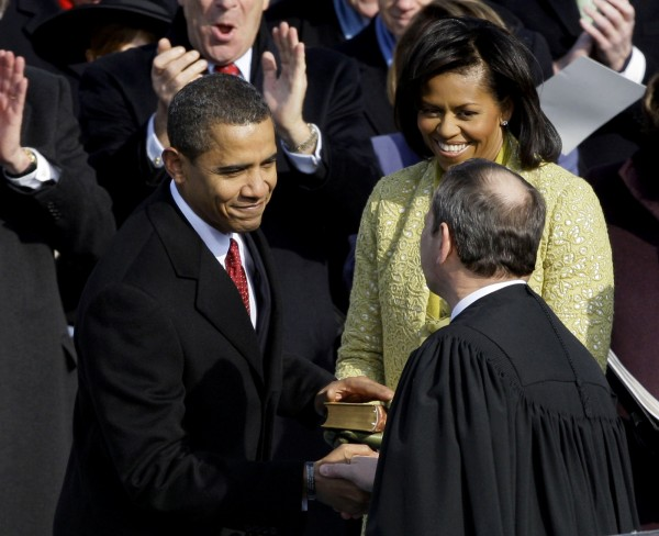 In this Jan. 20, 1989 file photo, President Barack Obama (left) shakes hands with Chief Justice John Roberts after taking the oath of office, on Capitol Hill in Washington. At right rear is first lady Michelle Obama. Breaking with the court's other conservative justices, Roberts announced the judgment that allows the law to go forward with its aim of covering more than 30 million uninsured Americans.