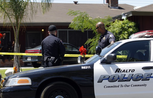 Two police officers stand in front of Rodney King's home in Rialto, Calif., Sunday, June 17, 2012. King, the black motorist whose 1991 videotaped beating by Los Angeles police officers was the touchstone for one of the most destructive race riots in U.S. history, died Sunday. He was 47. King's fiancee called police at 5:25 a.m. to report that she found him at the bottom of the swimming pool at their home in Rialto, California, police Lt. Dean Hardin said.