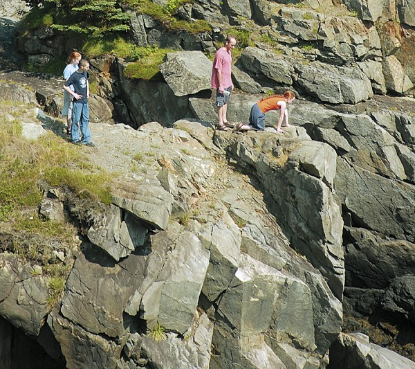 A venturesome hiker works her way to the edge of a cliff to peer into a chasm at Quoddy Head State Park in Lubec.